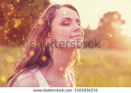 Young woman on field under sunset light Foto d'archivio ©