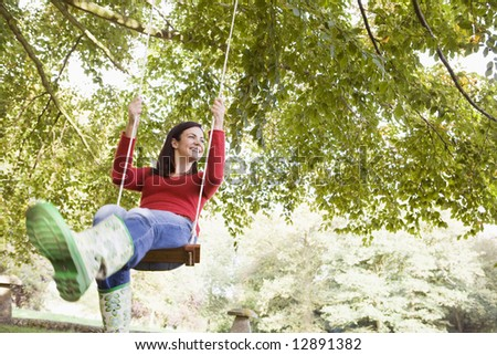Young woman on garden swing