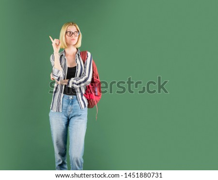 Young woman on green blackboard background - for text copy space. Portrait of college student in college.