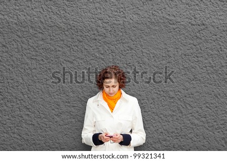 Young woman on grey wall with her smartphone