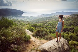 Young woman on holiday wearing denim summer dungaree shorts and sandals admiring panorama from hill overseeing bay in Tuscany, Italy