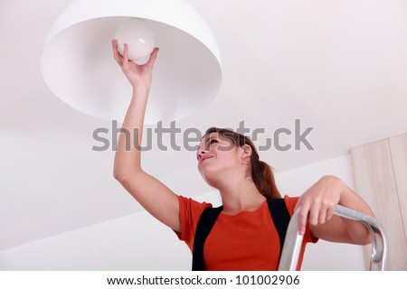 young woman on ladder changing bulb