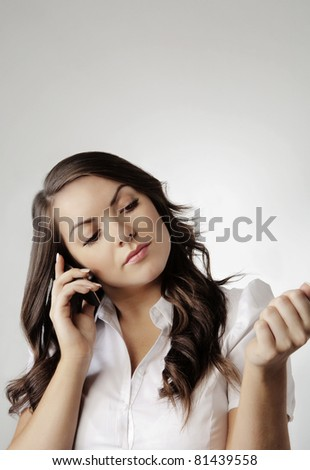 young woman on moblie telephone looking at her nails and talking