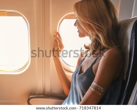 Young woman on passenger seat near window in airplane #718347814