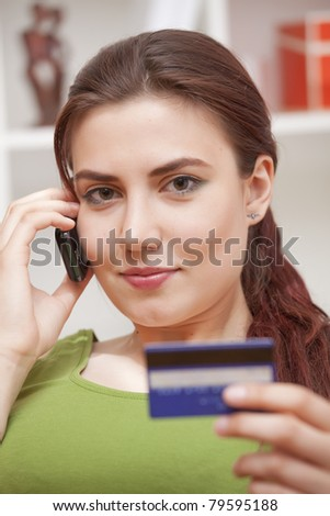 young woman on phone holding credit card at home