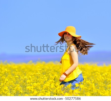 young woman on rapeseed field in bloom