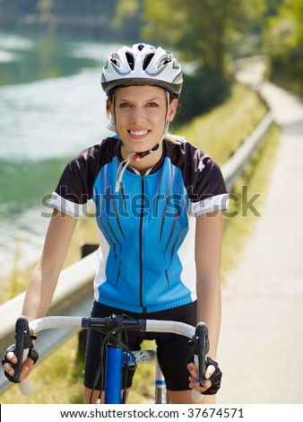young woman on road bike, looking at camera