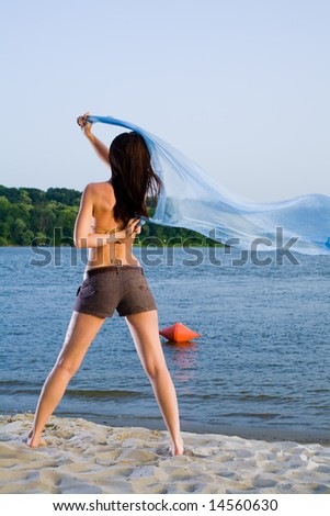 Young woman on sand beach near water with big cloth waving on wind