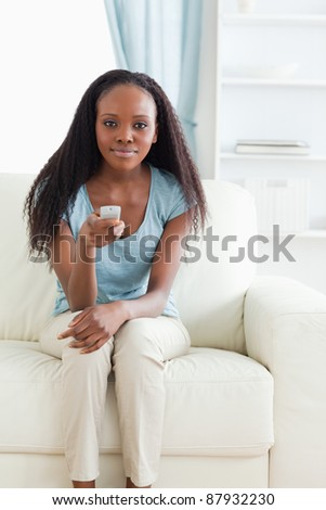 Young woman on sofa using remote control