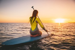 Young woman on stand up paddle board on a sea with warm summer sunset colors. Relaxing on ocean