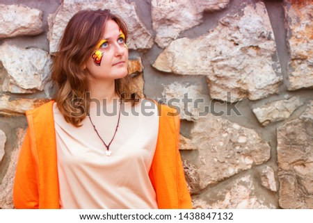 Young woman on stone wall background. A girl in a smart orange dress. Female portrait next to a wall of large stones. #1438847132