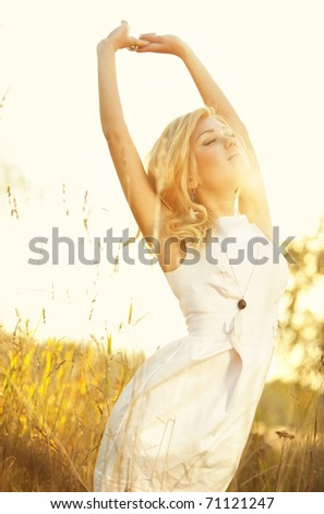 Young woman on summer field portrait. Bright sunlight effect.