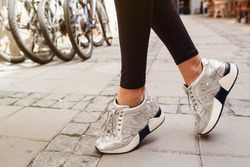 young woman on summer vacation, traveling around europe, close up of legs, wearing stylish silver sneakers, hipster street style, shoes details, bicycles on background