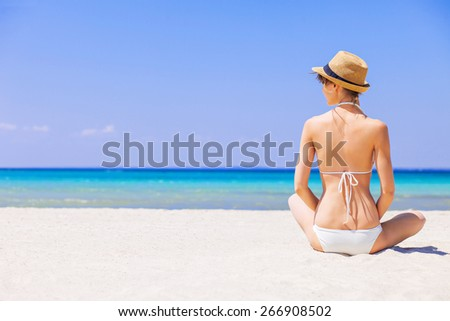 Young woman on the beach. Girl sitting on sand and sunbathing. Relaxation, rest, vacations, holidays, summer fun, enjoy life concept