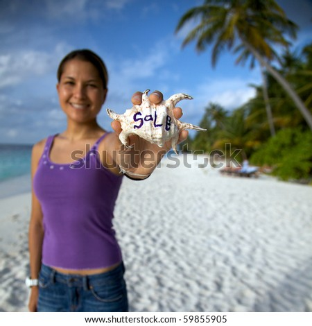 Young Woman On The Beach Holding A Shell In Her Hand With Sale Written On It!