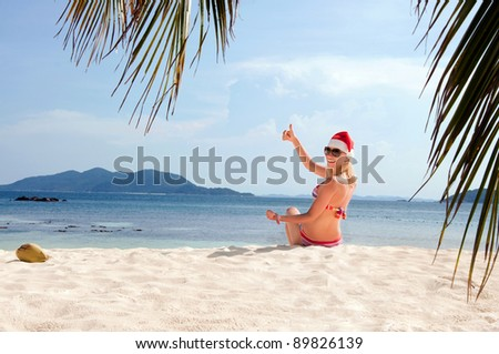 Young woman on the beach in santa's hat