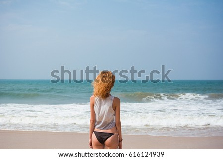 young woman on the beach near the ocean waiting for a wave, Sri Lanka #616124939