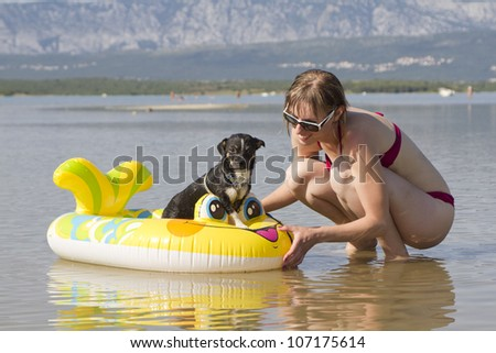 Young woman on the beach playing with dog