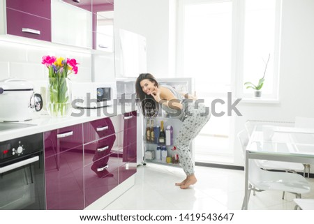 Young woman on the kitchen opening a fridge. Female indoors in the morning. Cheat meal. glutton girl.
