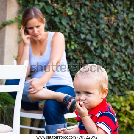 Young woman on the phone and a little boy outdoors.