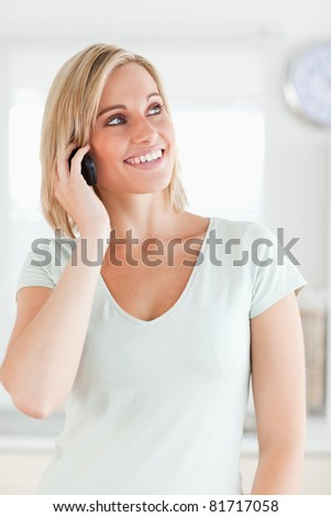 Young woman on the phone in the kitchen