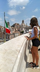 young woman on the terrace of the Victor Emmanuel II Monument. tourist looking at the flag of italy from above. Rome Europe Italia travel summer tourism holiday vacation background