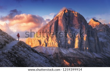 Young woman on the trail looking on high mountain peak at sunset in Dolomites, Italy. Autumn landscape with girl, path, rocks, sky with clouds at colorful sunset. Hiking in alps. Majestic mountains #1259399914