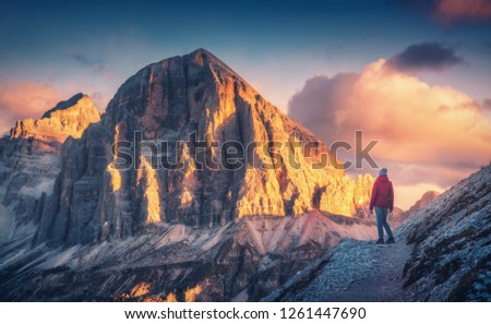 Young woman on the trail looking on high mountain peak at sunset in Dolomites, Italy. Autumn landscape with girl, path, rocks, sky with clouds at colorful sunset. Hiking in alps. Majestic mountains #1261447690