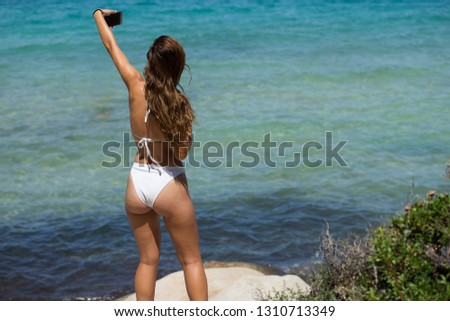 Young woman on top of a cliff taking a selfie picture, beautiful tanned female body, white bikini, sexy buttocks