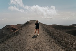 Young woman on top of a mountain photographing nature, hiking up on top of Mount Etna, photographer taking a picture