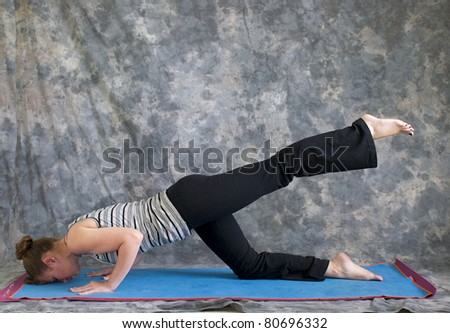 Young woman on yoga mat in  Yoga posture sunbird pose with left leg lifted, against a grey background in profile, facing left lit by diffused sunlight.