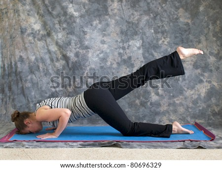 Young woman on yoga mat in  Yoga posture sunbird pose with right leg lifted, against a grey background in profile, facing left lit by diffused sunlight.