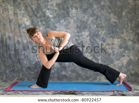 Young woman on yoga mat Yoga posture Parivrtta Parsvakonasana or Revolved Extended Side Angle pose with hands in prayer position against a grey background, facing left lit by diffused sunlight.