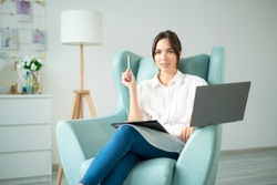 Young woman online coach sits home on chair with laptop and holds pen.