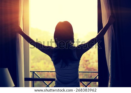 young woman opening curtains in ...