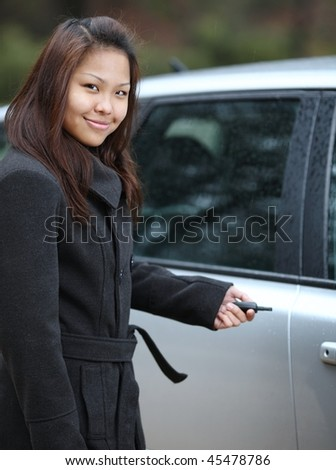 Young woman opening her new car with a remote