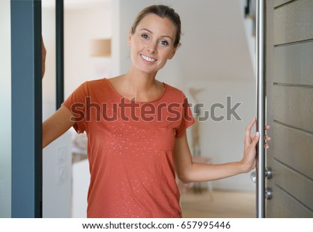 Young woman opening house front door to welcome people in