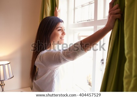 Young woman opens curtains to look at the view from a window