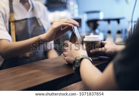 Young woman or barista serving customer at coffee shop.Takeaway and service concept, Small Business. Owner Business.