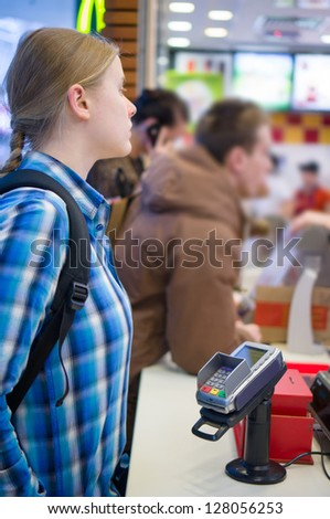 Young woman order meal in fast food restaurant