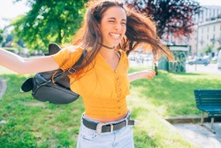 young woman outdoor having fun laughing spreading arms - getting away from it all, spontaneous, positive emotions concept