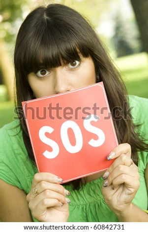 Young woman outdoors in the hands holding the red card with the text of SOS. Prayer in aid