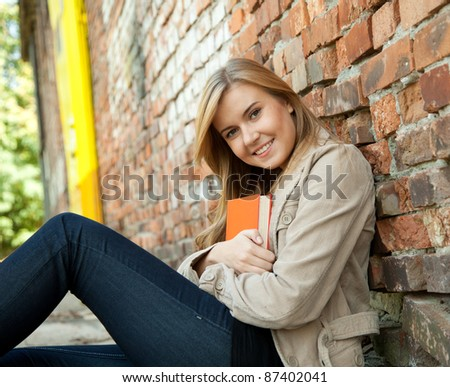 young woman outdoors leaning on the old bricks wall and keeping red book