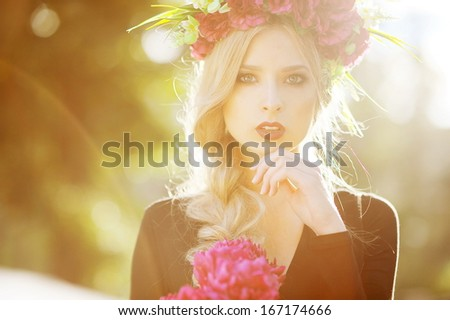 Young woman outdoors portrait. Soft sunny colors. with flowers in her hair