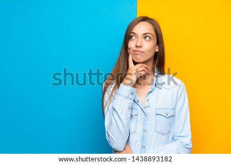 Young woman over colorful background thinking an idea