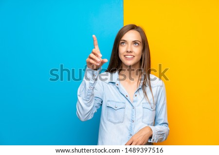 Young woman over colorful background touching on transparent screen #1489397516