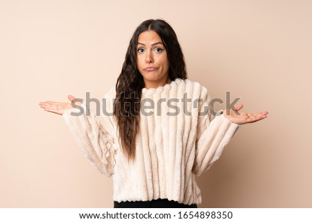 Young woman over isolated background having doubts while raising hands Photo stock ©