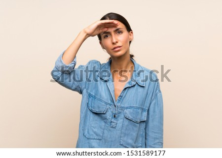 Young woman over isolated background looking far away with hand to look something