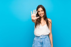 Young woman over isolated blue background counting five with fingers