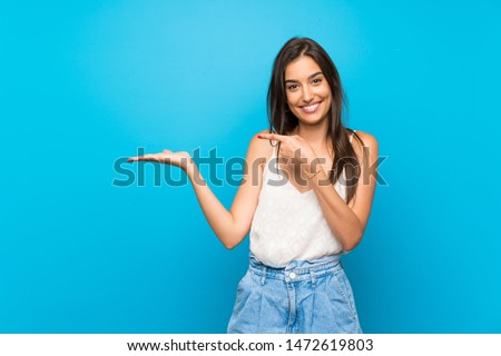 Young woman over isolated blue background holding copyspace imaginary on the palm to insert an ad